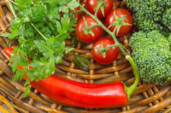 Cherry tomatoes with parsley, broccoli and pepper. Cherry tomatoes with parsley, broccoli and red pepper on a wooden plate Stock Images