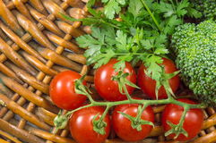 Cherry tomatoes with parsley and broccoli. On a wooden plate Royalty Free Stock Images