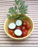 Cherry tomatoes, parsley and cucumbers. Fresh vegetables for salads pot in yellow Royalty Free Stock Photos