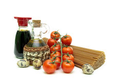 Cherry tomatoes, pasta, quail eggs, olive oil and soy sauce on w Stock Image