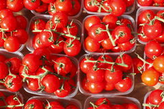 Cherry tomatoes in plastic bowls. On a market stall stock photo