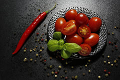 Cherry tomatoes on a plate with basil and chili pepper Stock Image