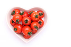 Cherry tomatoes on plate. Cherry tomatoes on heart shaped plate Stock Images