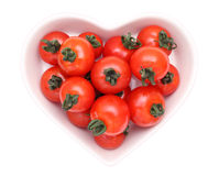 Cherry tomatoes on plate. Cherry tomatoes on heart-shaped plate isolated on white background Royalty Free Stock Image