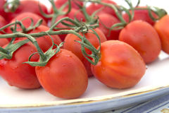 Cherry tomatoes plate tablecloth Stock Images