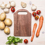 Cherry tomatoes, potatoes, carrots, parsley and mushrooms laid out around a cutting board place text,frame on wooden rustic ba Stock Photo