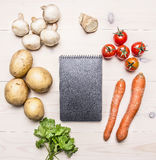 Cherry tomatoes, potatoes, carrots, parsley and mushrooms laid out around a notebook place text,frame on wooden rustic backgro Stock Photo