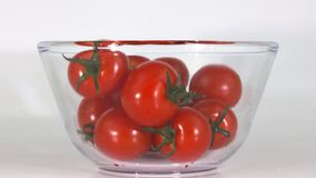 Cherry tomatoes are poured into a glass bowl stock footage