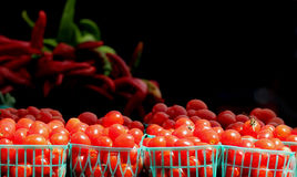 Cherry tomatoes produce in little baskets. A fresh produce stand is selling tomato vegetables in green little baskets. The background is blank for text area in Royalty Free Stock Image
