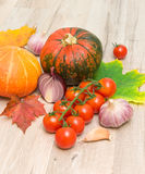 Cherry tomatoes, pumpkin and garlic on a wooden board Stock Photos