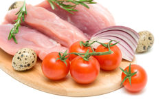 Cherry tomatoes, raw meat, eggs, onions and a sprig of rosemary. Ripe cherry tomatoes, raw meat, quail eggs, onion and rosemary on a cutting board on a white Stock Images