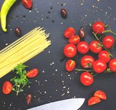 Cherry tomatoes and raw pasta on dark table. Cherry tomatoes and raw pasta on blackn table Stock Photography