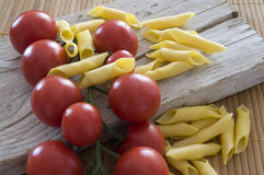 Cherry tomatoes and raw pasta Stock Image