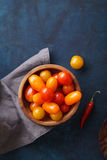 Cherry tomatoes and red pepper on blue background. Rustic concept Stock Images