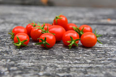 Cherry tomatoes. Red cherry tomatoes on a raw wooden background Royalty Free Stock Photos
