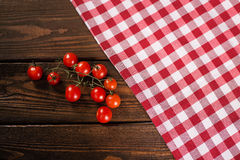Cherry tomatoes in a red tablecloth cell Stock Images