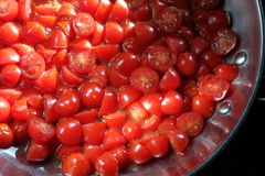 Cherry Tomatoes. Ripe summer harvest of cherry tomatoes begin to saute in the pan Royalty Free Stock Photos