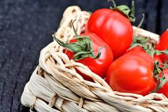 Cherry tomatoes in a rustic wicker on table Stock Photo