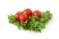 Cherry tomatoes on a salad leaf on white background. Several cherry tomatoes on fresh lettuce leaves on a white background Stock Photography