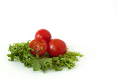 Cherry tomatoes on a salad leaf on white background. Several cherry tomatoes on fresh lettuce leaves on a white background royalty free stock image