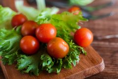 Cherry tomatoes and salad leaves on the cutting board with soft focus on the background. Top view. Copy text space. Cherry tomatoes and salad leaves on the Royalty Free Stock Image