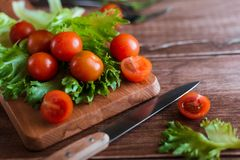 Cherry tomatoes and salad leaves on the cutting board with soft focus on the background. Top view. Copy text space. Cherry tomatoes and salad leaves on the Royalty Free Stock Photography