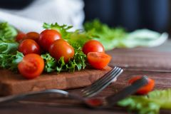 Cherry tomatoes and salad leaves on the cutting board with soft focus on the background. Top view. Copy text space. Cherry tomatoes and salad leaves on the Royalty Free Stock Photo