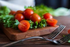 Cherry tomatoes and salad leaves on the cutting board with soft focus on the background. Top view. Copy text space. Cherry tomatoes and salad leaves on the Stock Photo