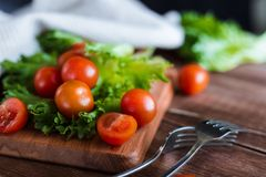Cherry tomatoes and salad leaves on the cutting board with soft focus on the background. Top view. Copy text space. Cherry tomatoes and salad leaves on the Royalty Free Stock Images