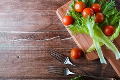 Cherry tomatoes and salad leaves on the cutting board with soft focus on the background. Top view. Copy text space. Stock Photo