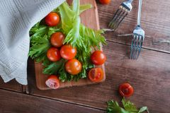 Cherry tomatoes and salad leaves on the cutting board with soft focus on the background. Top view. Copy text space. Stock Image