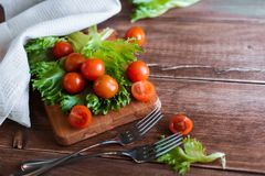 Cherry tomatoes and salad leaves on the cutting board with soft focus on the background. Top view. Copy text space. Cherry tomatoes and salad leaves on the Stock Photos
