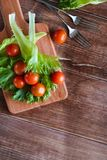 Cherry tomatoes and salad leaves on the cutting board with soft focus on the background. Top view. Copy text space. Royalty Free Stock Photography