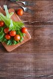 Cherry tomatoes and salad leaves on the cutting board with soft focus on the background. Top view. Copy text space. Stock Photos