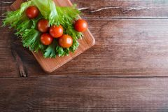 Cherry tomatoes and salad leaves on the cutting board with soft focus on the background. Top view. Copy text space. Royalty Free Stock Image
