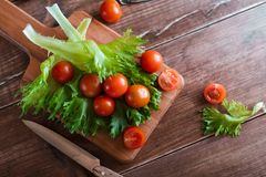 Cherry tomatoes and salad leaves on the cutting board with soft focus on the background. Top view. Copy text space. Royalty Free Stock Images
