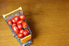 Cherry tomatoes in shopping cart Stock Photos
