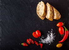 Cherry tomatoes on slate with sliced bread and salt Royalty Free Stock Photo