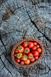 Cherry tomatoes in a small basket on an old wooden surface, spac Stock Photo