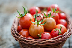 Cherry tomatoes in a small basket on an old wooden surface Royalty Free Stock Image