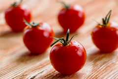 Cherry tomatoes. Small cherry tomatoes on the wooden background. Closeup, selective focus Stock Photography