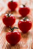 Cherry tomatoes. Small cherry tomatoes on the wooden background. Closeup, selective focus Stock Images