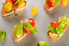 Cherry tomatoes and snow peas crostini Stock Photos