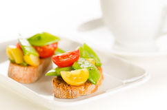 Cherry tomatoes and snow peas crostini with tea on white saucer Royalty Free Stock Images