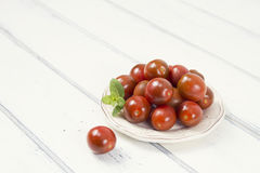 Cherry tomatoes. Some cherry tomatoes on a white wooden table. Vintage Style Royalty Free Stock Image