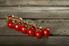 Cherry tomatoes. Some cherry tomatoes on a wooden surface royalty free stock photography