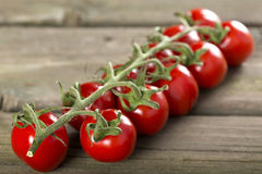 Cherry tomatoes. Some cherry tomatoes on a wooden surface stock photography