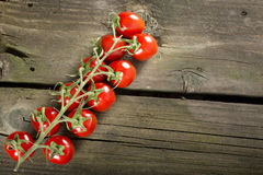 Cherry tomatoes. Some cherry tomatoes on a wooden surface with copy space royalty free stock image