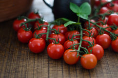 Cherry Tomatoes on Stalks. Some cherry tomatoes on dark oak board with clay jug in background Stock Photography