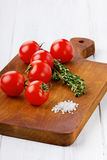 Cherry tomatoes with a thyme and sea salt. On a kitchen board on a white wooden surface Royalty Free Stock Photos